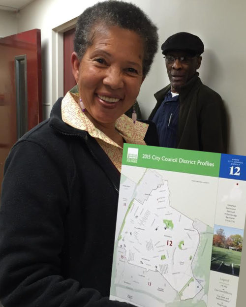 An open space steward holds the District Profile for her City Council district in the Bronx