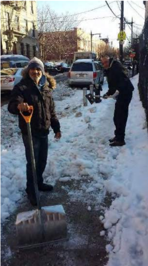 "Gardeners shoveling snow off the sidewalks around the Jardin de la Roca in Melrose, in the Bronx. Photo by Salvador Dominguez. Original caption: ""Shoveling snow at Jardin de la Roca. Photo by Salvador Dominguez, GreenThumb community gardener at Jardin de la Roca."" Retrieved from the 2019 GreenThumb Gardeners' Handbook at https://greenthumb.nycgovparks.org"