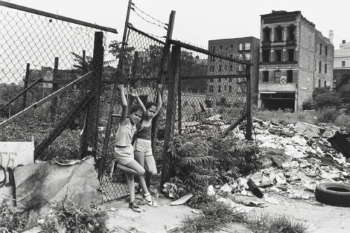 Two young girls cling to a fence by an empty lot in the South Bronx in the 1970s. Photo by Mel Rosenthal, displayed at the Museum of the City of New York. Retrieved from https://www.dnainfo.com